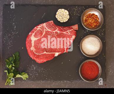 Raw fresh meat rib eye steak and seasonings on black stone slate background. Top view, blank space, vintage toned - Stock Photo