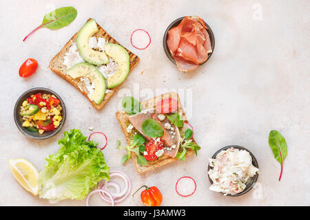 Open wholemeal sandwiches and various ingredients on rustic surface. Top view, blank space - Stock Photo