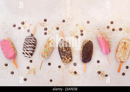 Ice cream sticks with chocolate, fruit, roasted almonds and colourful sugar sprinkles on rustic background. Top - Stock Photo