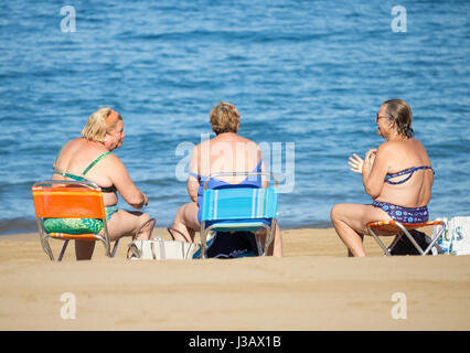Three elderly Spanish woman chatting on beach after morning swim. - Stock Photo