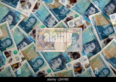 Swansea, UK. 4th May, 2017. An old £5 note resting on a bed of new ones. The £5 banknote, featuring prison reformer - Stock Photo