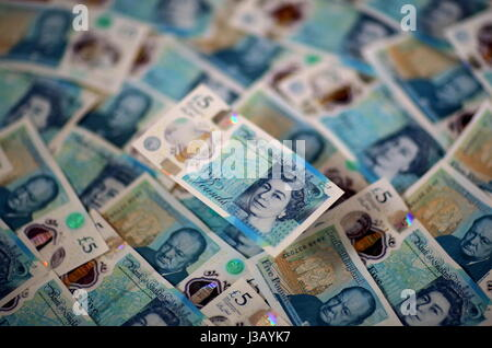 Swansea, UK. 4th May, 2017. A £5 note resting on a bed of new ones. The £5 banknote, featuring prison reformer Elizabeth - Stock Photo