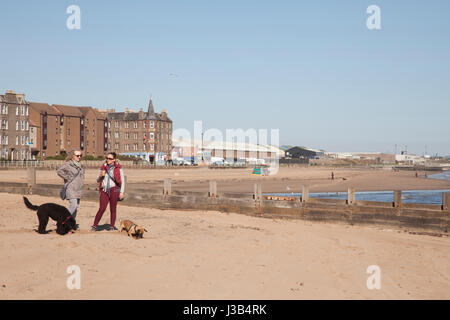 Portobello beach, Edinburgh, UK. 5th May, 2017. Two women standing with coffe. With dogs around playning on the - Stock Photo