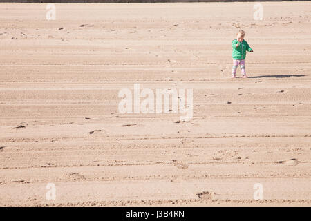 Portobello beach, Edinburgh, UK. 5th May, 2017. Baby girl standing on the sand of Portobello beach on a lovely sunny - Stock Photo