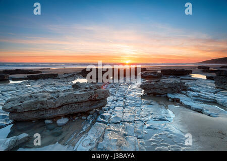 Sunset over limestone pavements at Dunraven Bay in the Vale of Glamorgan in Wales - Stock Photo