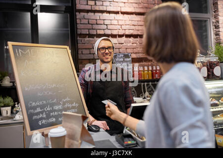 barman and woman paying with credit card at cafe - Stock Photo