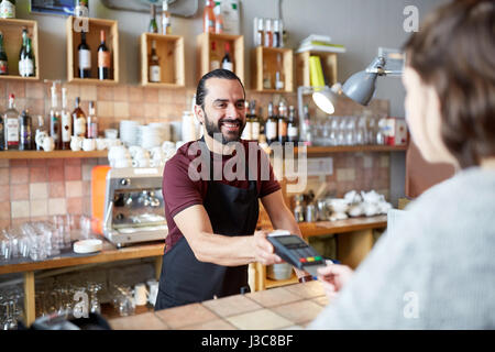 man or waiter with card reader and customer at bar - Stock Photo