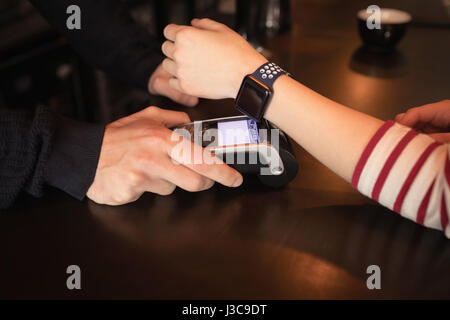 Woman paying through smartwatch using NFC technology in café - Stock Photo