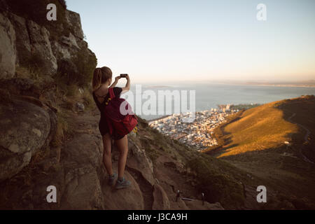 Rear view of woman taking a photo with a camera - Stock Photo