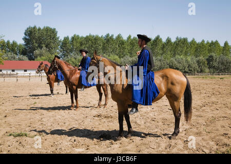Chicos in traditional blue costume at a horse farm in the Puszta region of Hungary, Europe. - Stock Photo