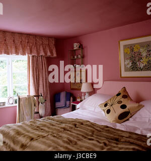 1940s style cushion on double bed with fur throw. - Stock Photo