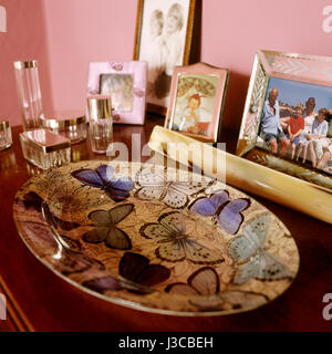 Perfume bottles and family photograph with butterfly dish - Stock Photo