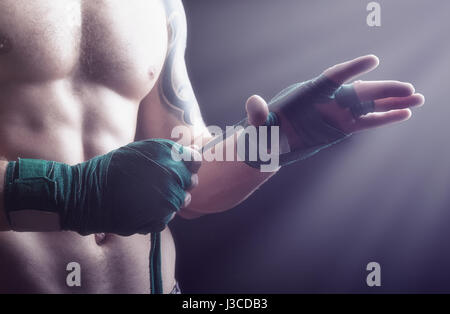 Close up of a boxer putting on straps preparing for combat - Stock Photo