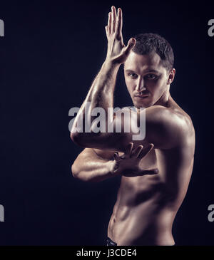 Young handsome man practicing martial arts on a black background - Stock Photo