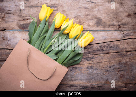 Bunch of yellow tulips in paper bag on wood background. Spring or mothers day background