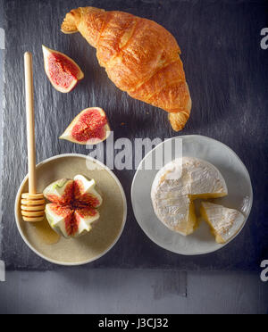 Croissant with soft cheese and figs on a stone plate - Stock Photo