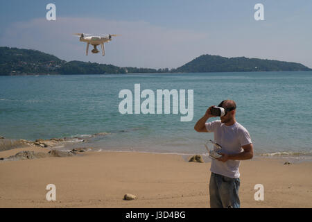 Young man wearing virtual reality glasses standing on the beach with remote controller of drone over sea and sky - Stock Photo