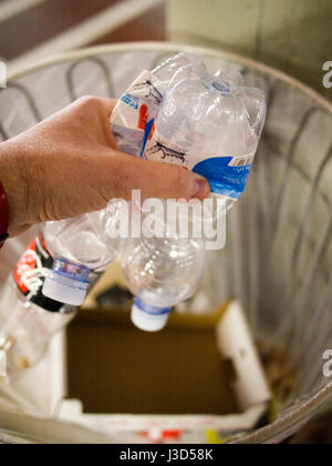 Putting plastic waste in the mixed trashcan - Stock Photo