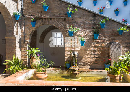 patio with blue pots with flowers and green plants with water fontain in small pond in spain - Stock Photo