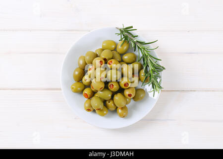 plate of green olives stuffed with red pepper on white background - Stock Photo