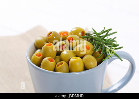 cup of green olives stuffed with red pepper - close up - Stock Photo