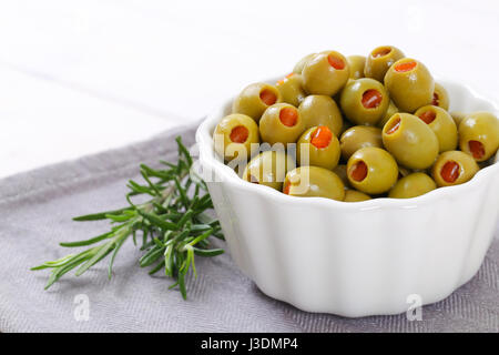 bowl of green olives stuffed with red pepper on grey place mat - close up - Stock Photo