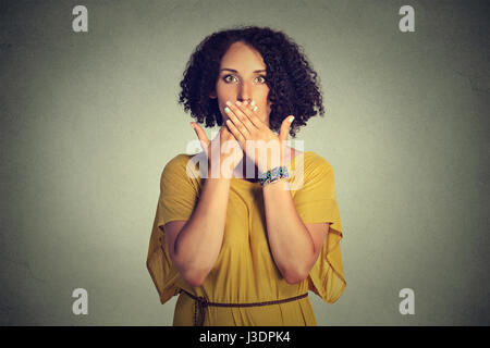 Closeup portrait young woman covering closed mouth with hands. Speak no evil concept isolated on grey wall background. - Stock Photo