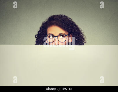 Banner sign woman peeking over edge of blank empty paper billboard with copy space for text. Beautiful woman in - Stock Photo