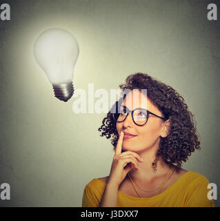 Closeup portrait beautiful woman thinks looking up at bright light bulb isolated on gray wall background. Idea, - Stock Photo