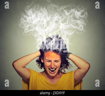 Portrait young stressed woman screaming frustrated thinking too hard steam coming out up of head isolated on grey - Stock Photo