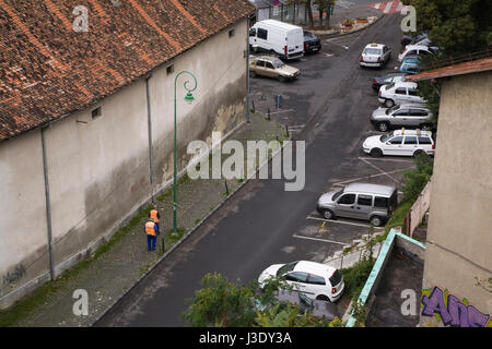 City workers cleaning a street in the town of Brasov, Romania, Eastern Europe - Stock Photo