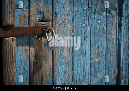 padlock on an old wooden door painted blue - Stock Photo