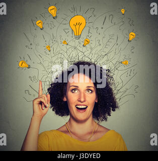 Closeup excited woman with many ideas light bulbs above head looking up pointing finger up isolated on gray wall - Stock Photo