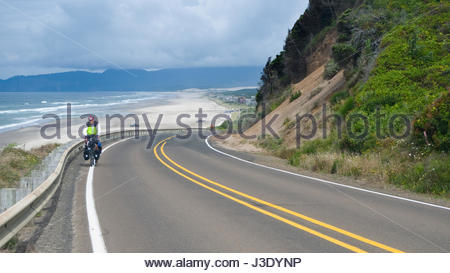 Man peddling a fully loaded touring bicycle up a hill along the coast of Oregon south of  Tierra Del Mar, Tillamook - Stock Photo