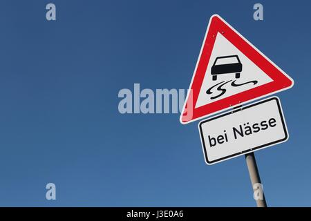 German road sign: slippery when wet - Stock Photo