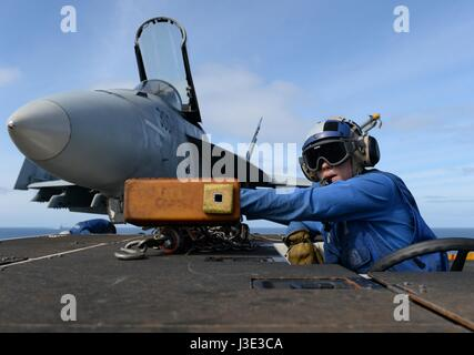 A U.S. soldier moves a USN F/A-18E Super Hornet fighter jet on the flight deck aboard the USN Nimitz-class aircraft - Stock Photo