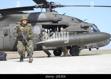 Romanian Army soldiers depart from a U.S. Army UH-60 Black Hawk helicopter during an air assault training mission - Stock Photo