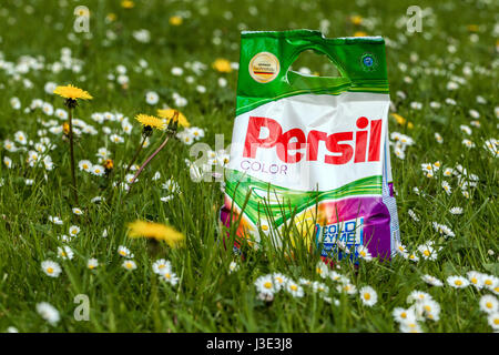 Persil washing powder on a meadow full of dandelions and daisies