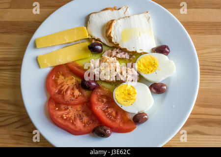 A cold antipasto selection: mozzarella, tomato, olives, hard-boiled egg, tuna, Pecorino Romano - Stock Photo