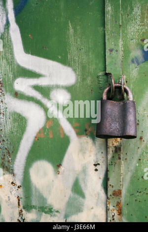 Old padlock on a background of painted doors - Stock Photo