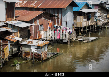 Basic simple dwellings in the form of wooden shacks or houses which the riverine people of Kalimantan live in beside - Stock Photo