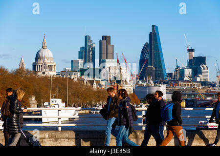 London, UK - March 13, 2017 - City of London seen from Waterloo Bridge with blurred pedestrians in the foreground - Stock Photo