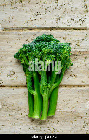 high-angle shot of some stems of broccolini on an off-white rustic wooden table - Stock Photo
