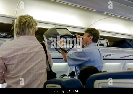 MiamiMiami Florida International Airport airline passenger overhead compartment luggage carry-on jet boarding Delta - Stock Photo