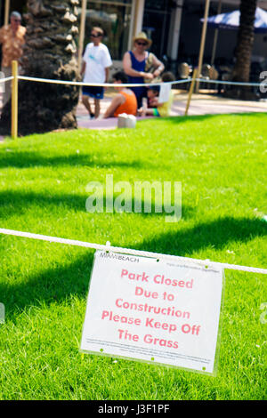 Miami Beach Florida Lincoln Road sign warning keep off. grass roped off park closed construction - Stock Photo
