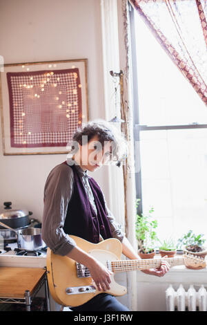Young woman playing a guitar - Stock Photo