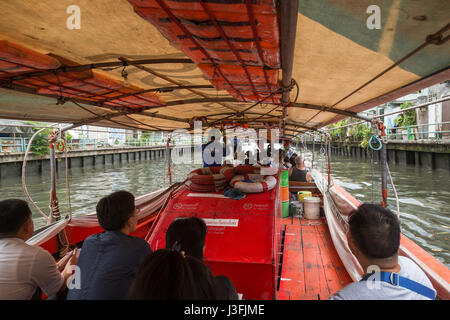 Several people on a khlong canal boat in Bangkok, Thailand. - Stock Photo