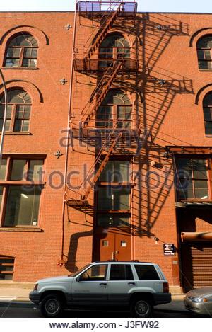 Metal fire escape on outside of red brick building, Portland, Multnomah County, Oregon, USA - Stock Photo