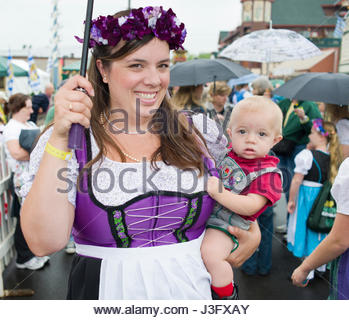 Mature Caucasian women in a traditional Germanic Dirndl Dress holding small child wearing lederhosen at the Mt. - Stock Photo