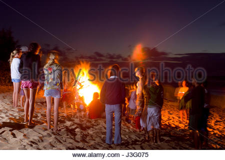 Friends And Family Enjoying A Bonfire On The Beach At Night Kaunala North